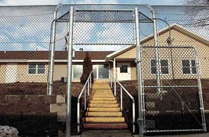 An eight-foot tall chain-link fence featuring no-climb mesh and an motion-sensor alarm system surrounds the Pendleton House on the campus of the Eastern Oregon Training Center in Pendleton.