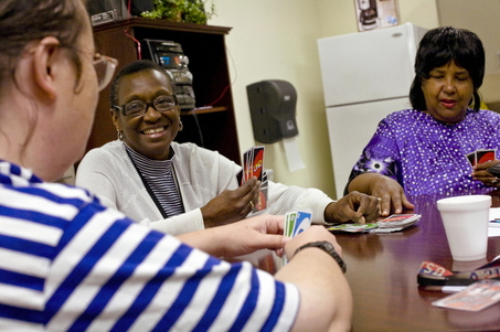 Gladys Howard of the Garlington Center plays Uno with clients Roxanne Taylor (left) and Sharon King.