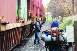 Christopher Schiller looks back towards his friends Claudia Lavadour and Brian Bettencourt as a train rumbles down the tracks recenlty in Pendleton.