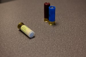 A yellow shotgun round containing a beanbag is displayed in front of two lethal types of police shotgun ammunition: The blue holds a slug and the red contains buckshot. 