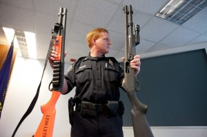 "Training Commander Robert Day holds up a less-lethal shotgun (left) and a standard shotgun. The less-lethal shotgun's stocks and pump grips are conspicuously painted orange, and marked ""less lethal"" to differentiate it from a standard shotgun."
