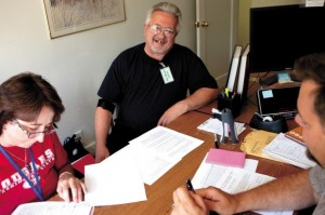 Mike Szpakiewicz is all smiles as he signs a lease on an apartment recently. To the left is his landlady, Rachel Perry, and in the right foreground is case manager Kevin Nixon of the Longview Housing Authority.