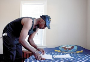 Will, a Navy veteran, sorts college English assignments as he settles in to a local home where he lives as part of the Veterans Integration Program for homeless vets, run by the Longview Housing Authority.