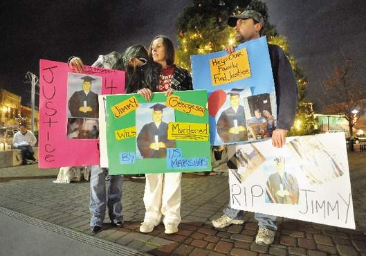 "Chelsea Walker, Lisa Bauer and Alan Sherwood hold signs in Vogel Plaza Saturday night in memory of James ""Jimmy"" Georgeson, 20, who was shot and killed Thursday by U.S. Marshals in Medford."