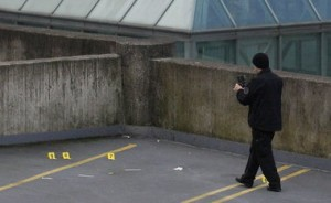 A Portland police officer investigates the police-involved shooting on the roof of a downtown parking garage.