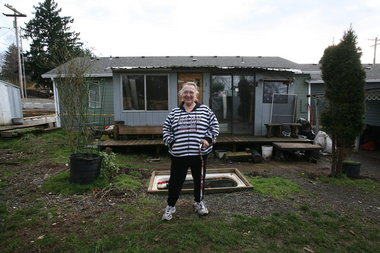 "Ethel ""Punki"" McNamee, 69, stands in front of one of four structures on her property that she rents to homeless people. She has been cited for code violations and ordered to evict her tenants by April 15."