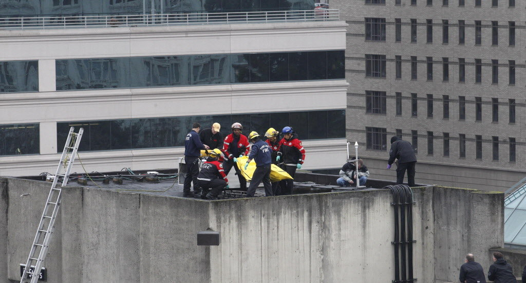 Portland firefighters move the body of a man shot by police Jan. 25 on the roof of a downtown Portland parking garage.