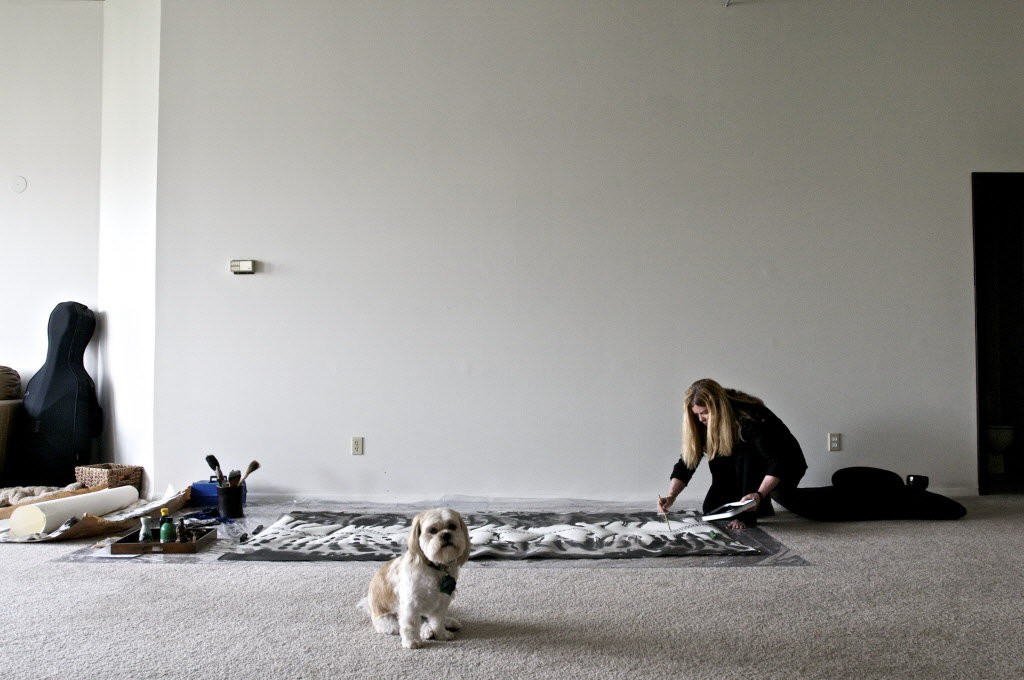 Meghan Caughey works on a sumi-e piece (Japanese for black ink painting) in her studio apartment, with her dog, Ananda. (Benjamin Brink / The Oregonian)