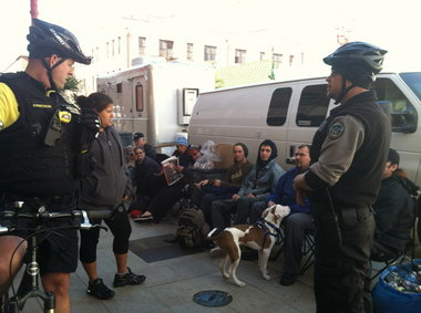 Portland Bicycle Police stop to visit with people waiting for a shower in Portland's Chinatown. Business owners in the vicinity have complained that the shower truck is hurting their businesses.
