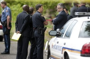 Portland Police Chief Mike Reese, middle, talks with then-Mayor Sam Adams, right, who showed up at the scene on Southwest Naito Parkway on June 30, 2011, soon after learning of Officer Dane Reister's shooting of William Kyle Monroe.
