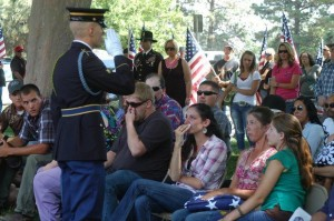 At the funeral service for Brady Hammer in Klamath Falls this summer, Travis Nelson, a cousin of Hammer's delivers the salute to Marie Hammer, Brady's mother, who holds the folded flag in her lap.