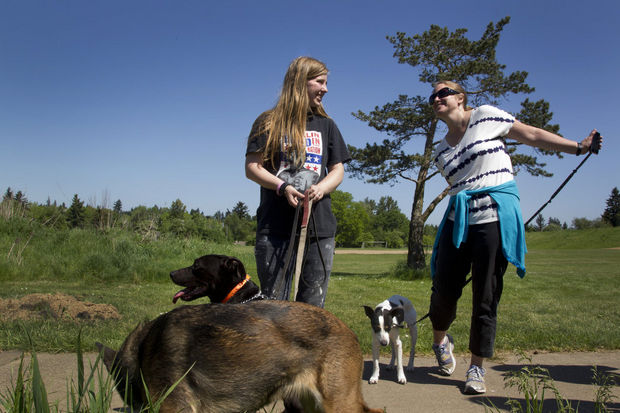 Melanie Carlson (L) walks her dogs, with therapist Kari Ault .