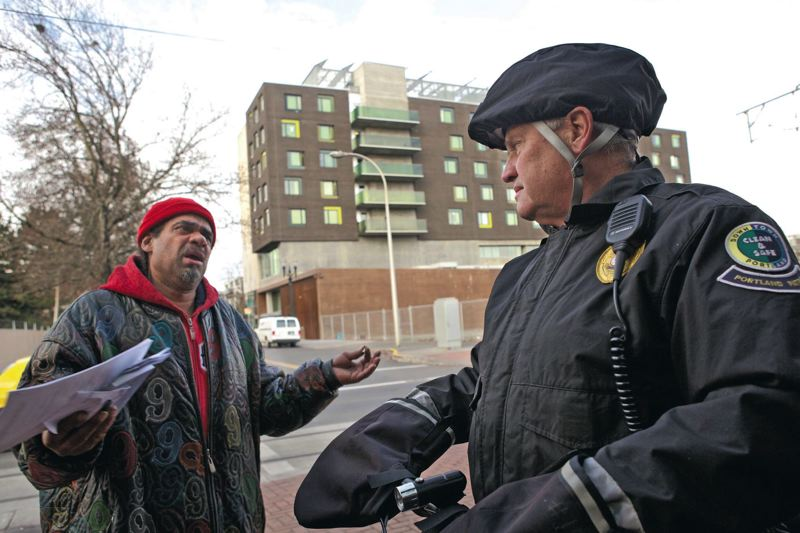 Portland Police Officer Jim Bare talks to Eric Turner with Bud Clark Commons in the background.