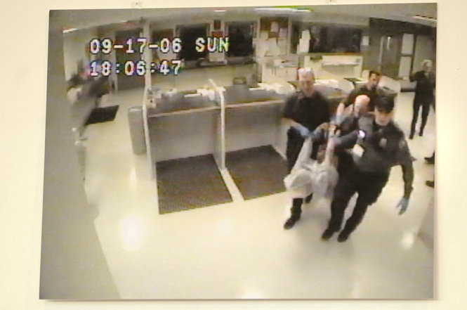 Police carry a hog-tied, hooded James Chasse to a jail cell.