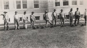 Groundsmen stand with lawnmowers in front of the Oregon State Hospital, 1910.