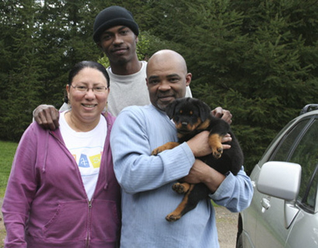 Prior to the tragedy, Keaton Otis stands in back, flanked by his mother and stepfather (holding the family dog, Hanna).
