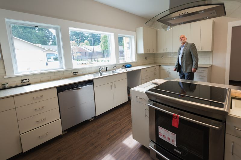 CEO Chris Krenk tours the kitchen of an intensive treatment group home in Gresham