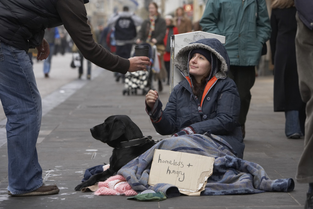 Person giving cup to homeless woman