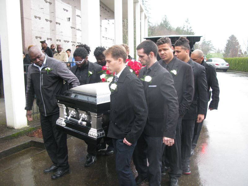 Chris Kalonji's casket is carried to the funeral site