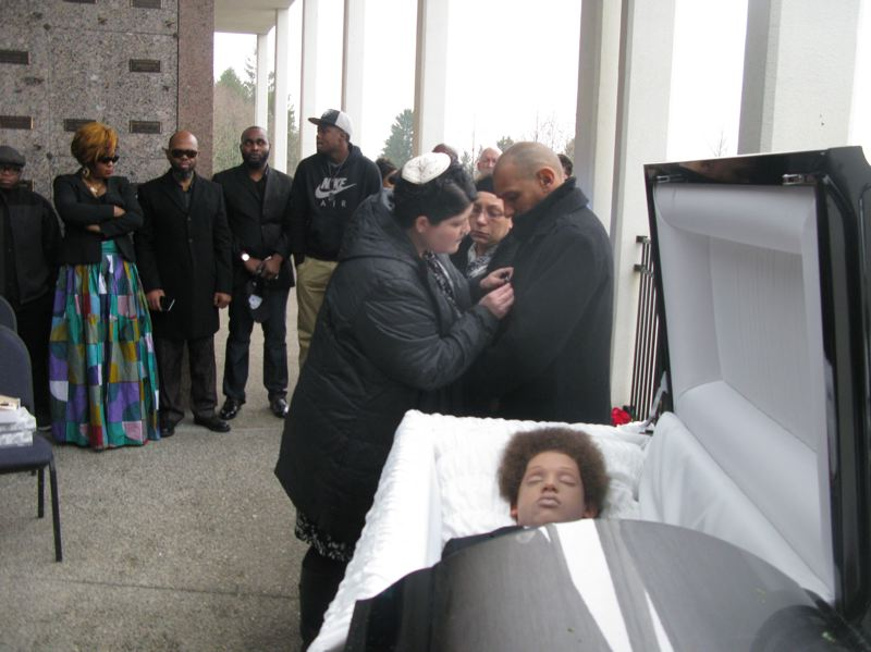 Rabbi Rachel Joseph of Congregation Beth Israel helps Tony and Irene Kalonji put on mourning ribbons during their son's funeral